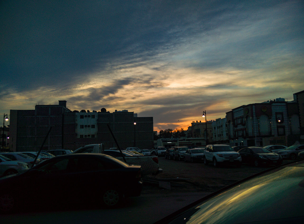 car, architecture, building exterior, built structure, city, transportation, sunset, sky, land vehicle, cloud - sky, no people, outdoors, cityscape, day