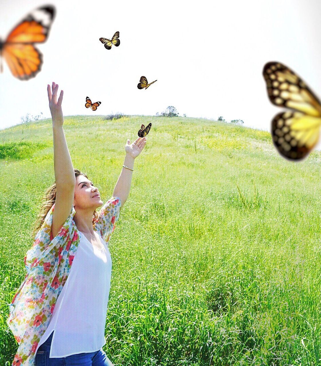 animal themes, bird, leisure activity, grass, nature, flying, arms raised, day, field, motion, outdoors, animal wildlife, animals in the wild, real people, one person, young adult, fun, one animal, mid-air, young women, standing, happiness, lifestyles, smiling, clear sky, beauty in nature, sky, people
