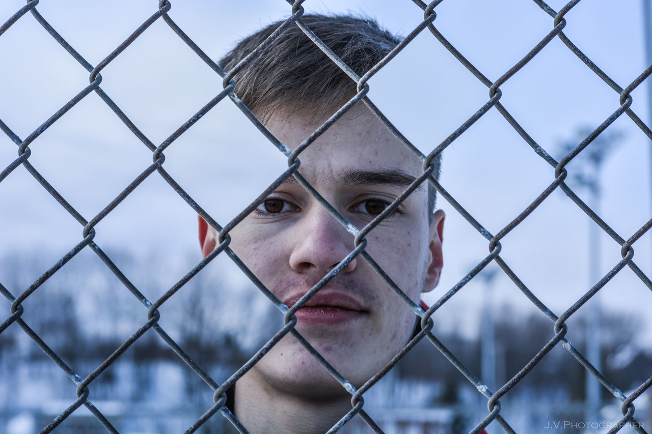 Adult Chainlink Fence Concealment Day Fence Headshot Hiding Holes Human Body Part Men Metal Missing Parts Mourning One Man Only One Person Only Men Outdoors People Phenomenon Prison Public Sky Special Effects Track And Field Stadium Watching