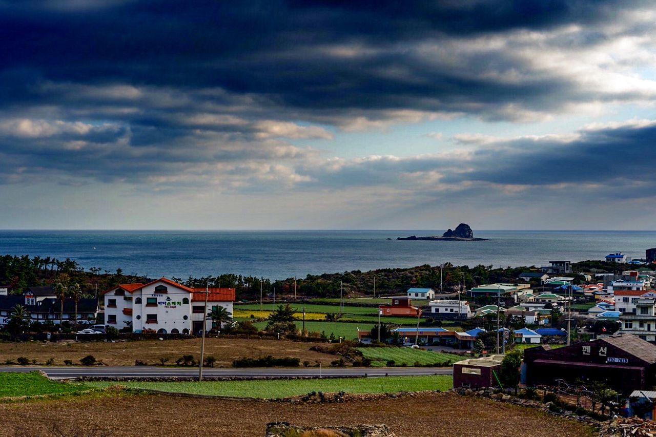 Houses On Landscape Against Calm Sea