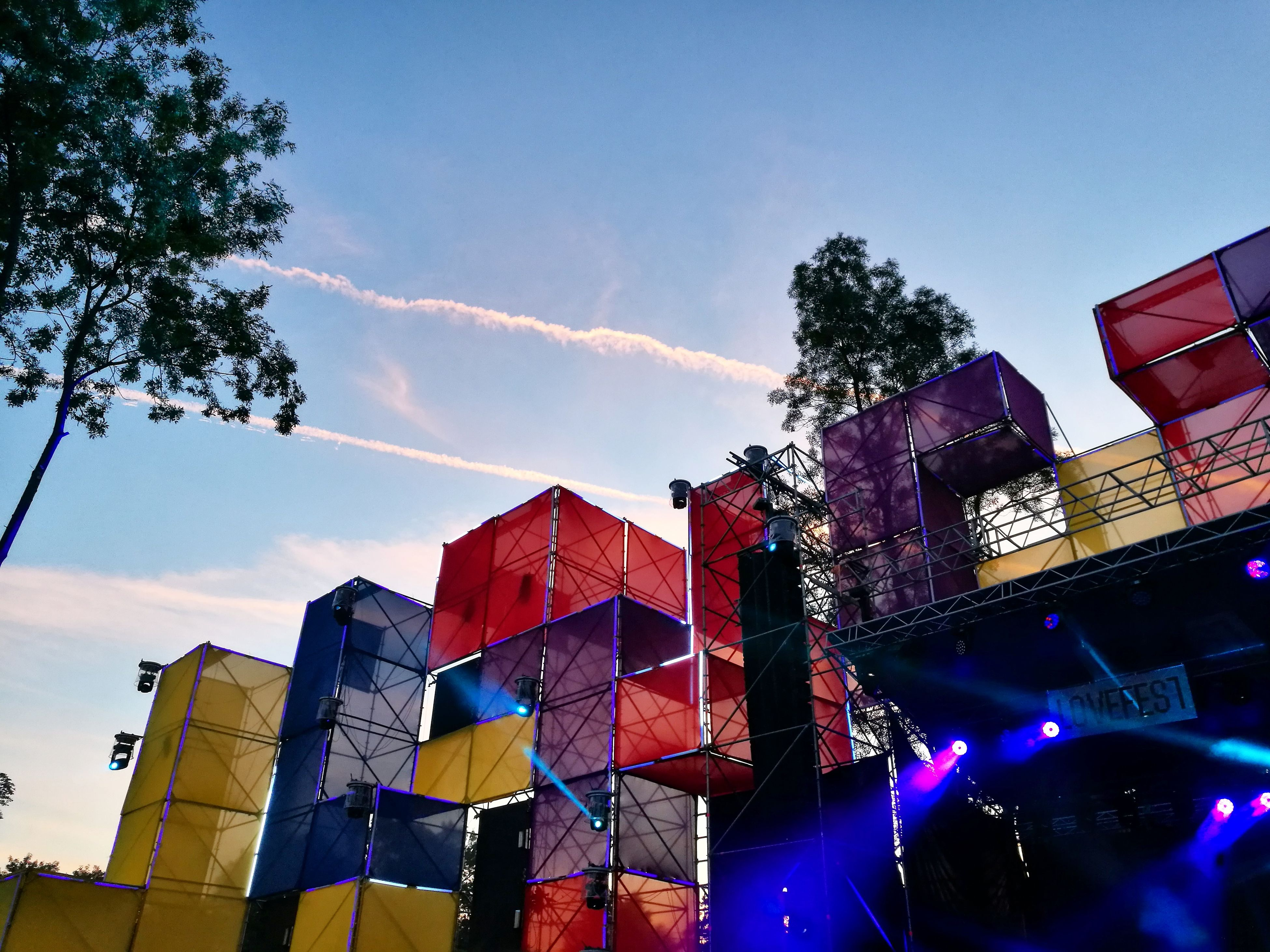 low angle view, building exterior, architecture, built structure, outdoors, multi colored, tree, sky, arts culture and entertainment, day, city, crowd