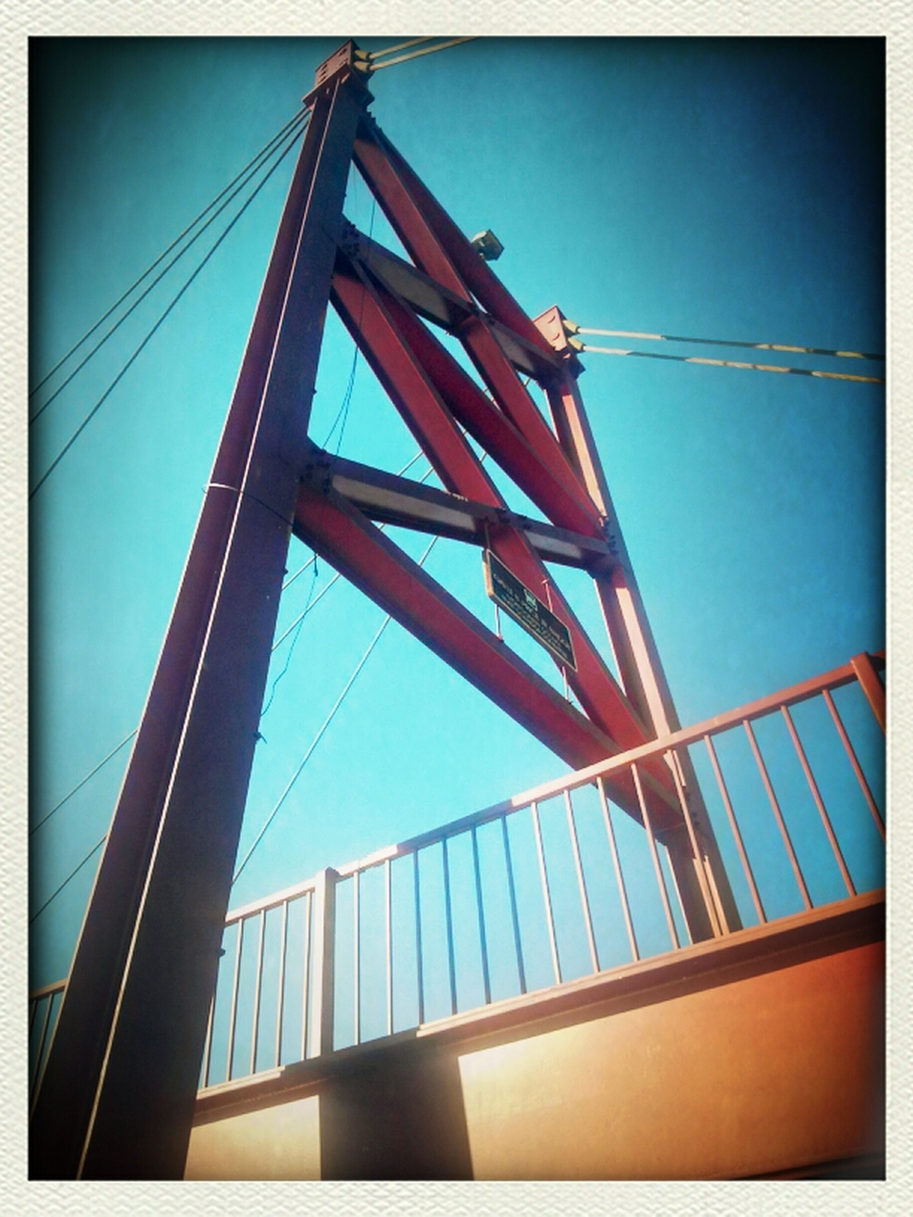 architecture, low angle view, built structure, connection, transfer print, bridge - man made structure, sky, suspension bridge, auto post production filter, engineering, bridge, cable, building exterior, clear sky, blue, no people, outdoors, city, day, modern