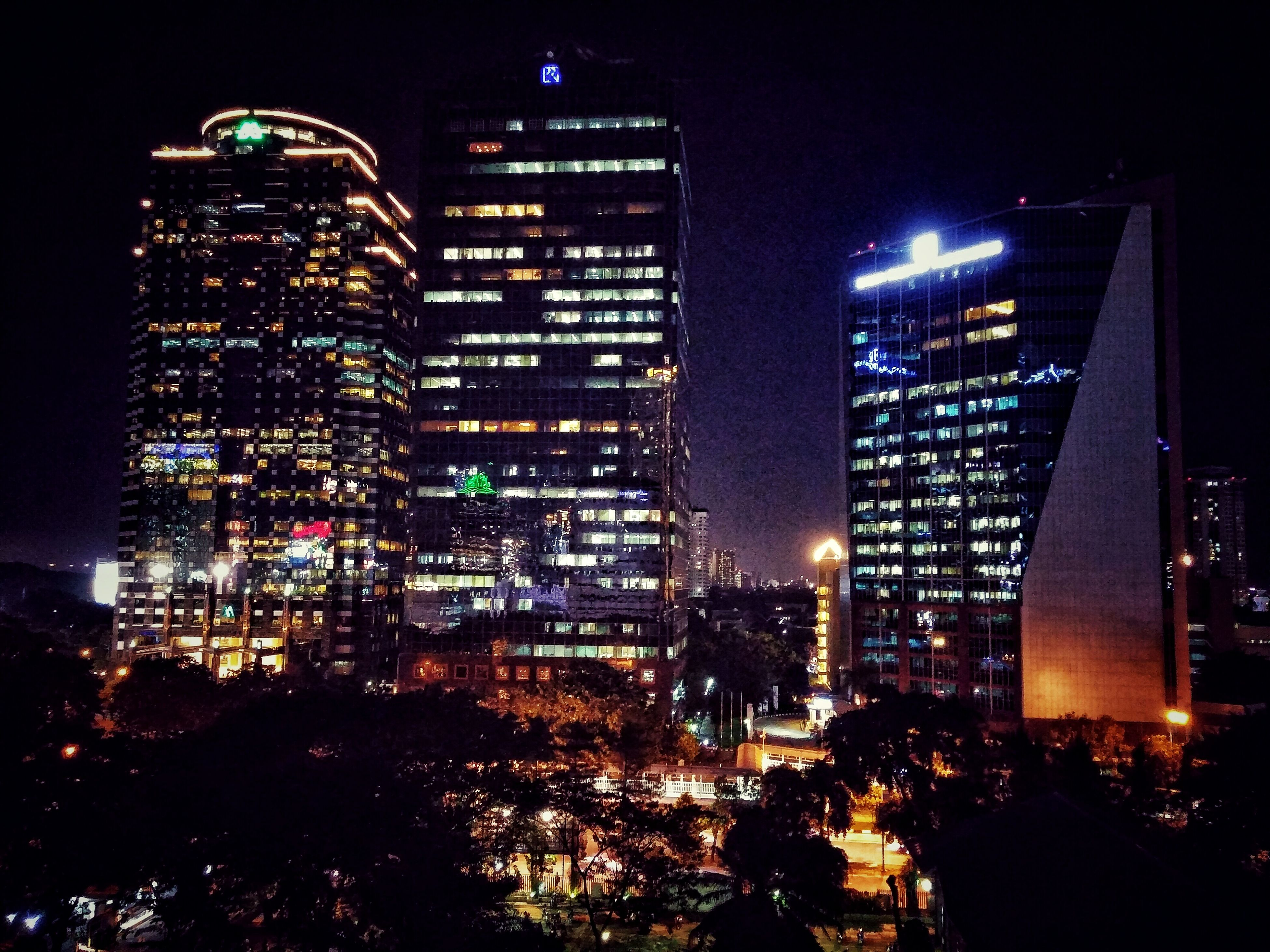 illuminated, night, building exterior, architecture, city, built structure, skyscraper, modern, tall - high, tower, cityscape, office building, city life, capital cities, financial district, dark, light - natural phenomenon, sky, crowded, lighting equipment