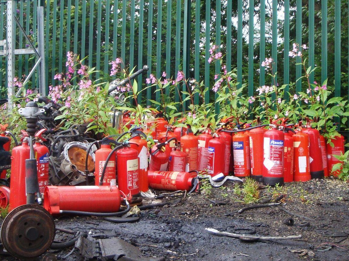 Scrapyard in Manchester Abandoned Fire Extinguishers Outdoors Red Redundant Scrap Metal Scrapyard