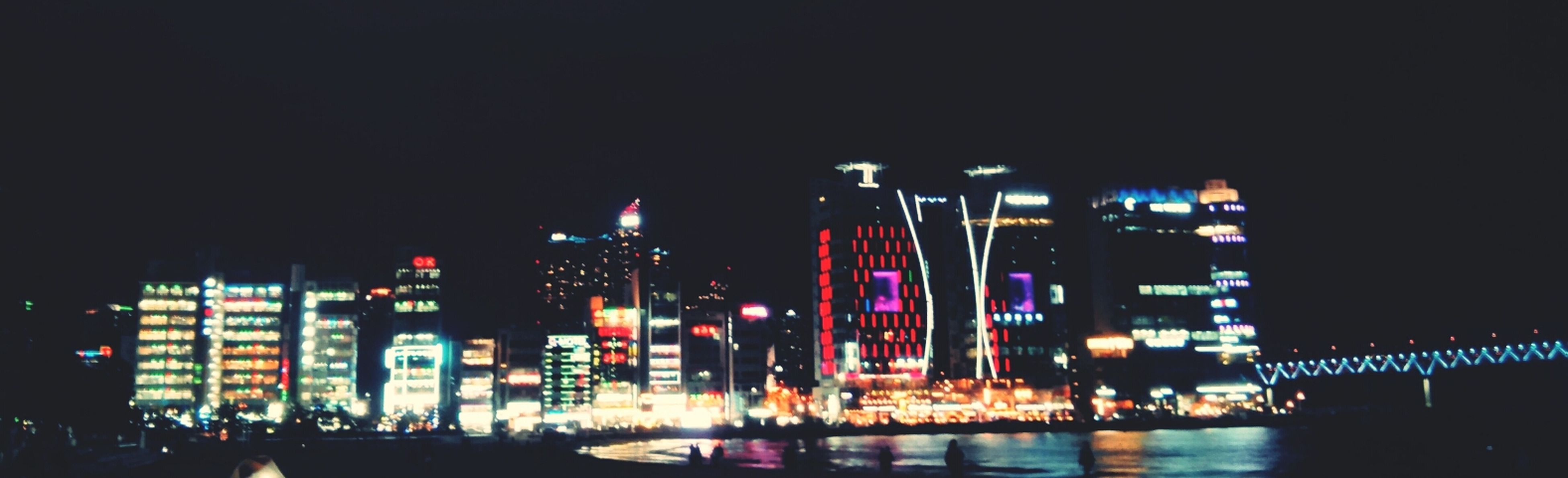 illuminated, night, building exterior, city, architecture, built structure, skyscraper, cityscape, modern, city life, office building, urban skyline, tall - high, tower, clear sky, reflection, water, lighting equipment, capital cities, travel destinations