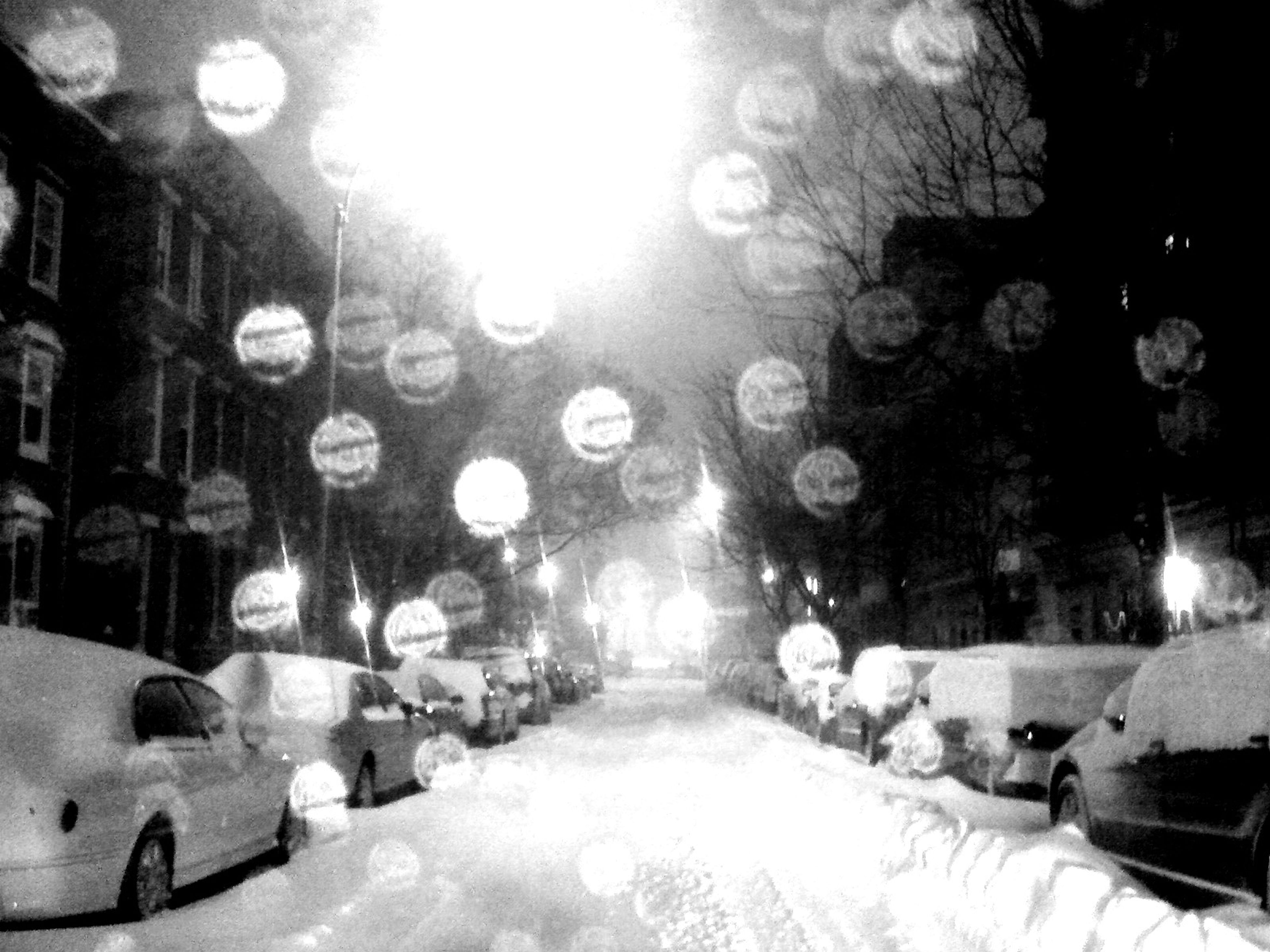 snow, cold temperature, winter, illuminated, season, night, weather, lighting equipment, indoors, covering, built structure, street, architecture, incidental people, frozen, in a row, the way forward, street light, diminishing perspective, building exterior