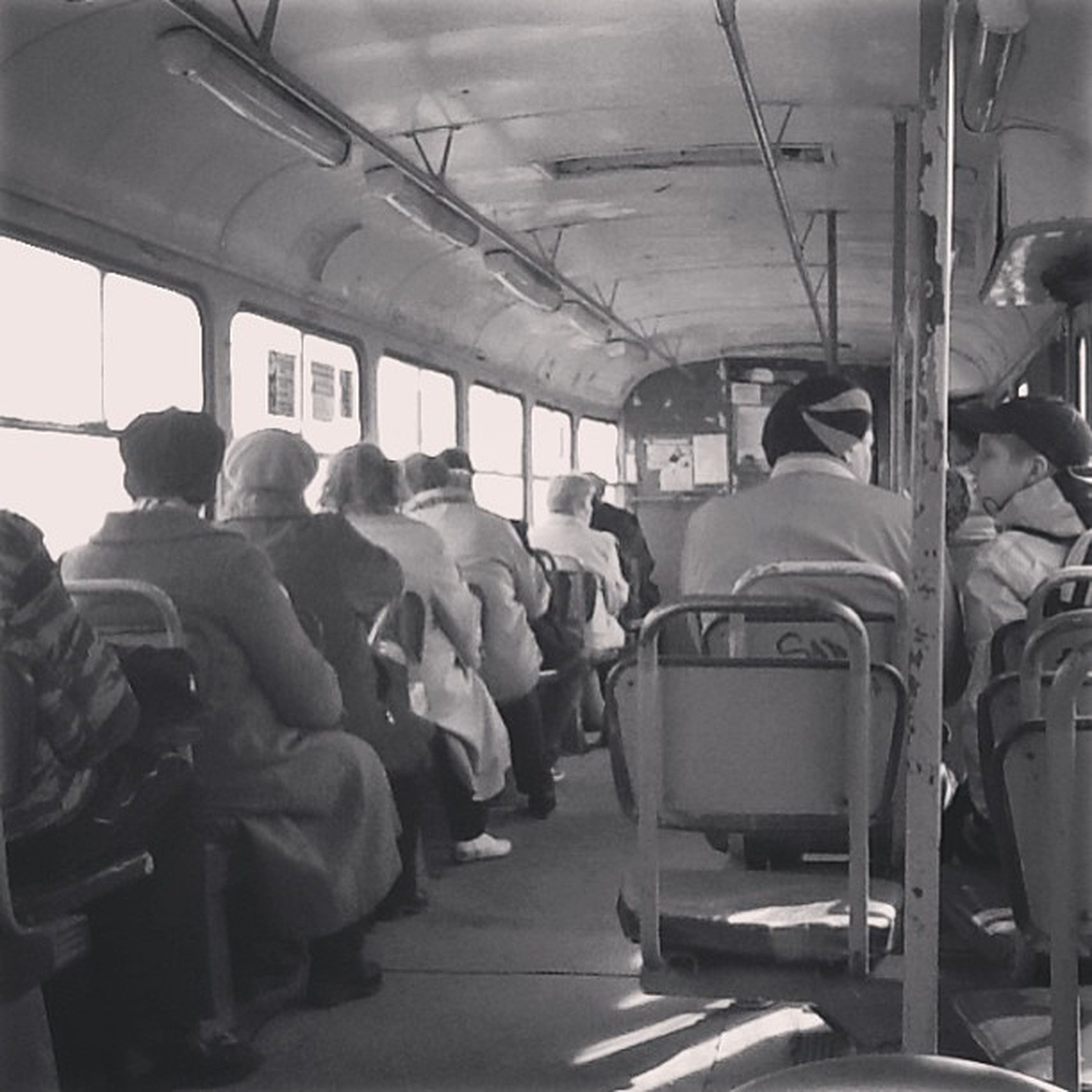 men, indoors, transportation, lifestyles, person, mode of transport, public transportation, travel, passenger, large group of people, journey, sitting, leisure activity, rear view, vehicle interior, medium group of people, vehicle seat, occupation, casual clothing