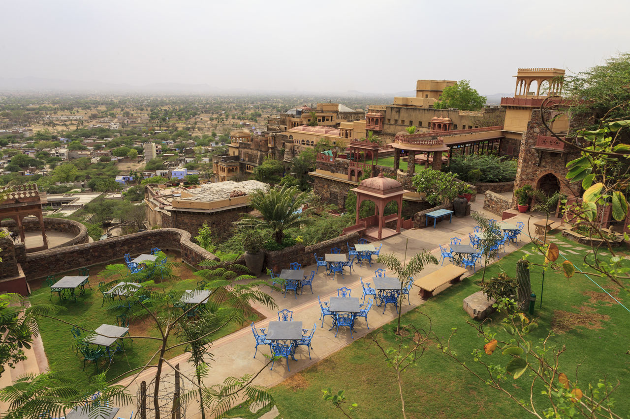 Elevated view of the lawn at the Neemrana Fort Palace in Alwar, Rajasthan, India. Architecture Beautiful Birdseye View Chairs Day Elevated View Historical Hotel India Landscape Mountain Neemrana Fort Neemranafortpalace No People Outdoors Rajasthan Resort Sky Tables Topofmountain Travel Travel Destinations Travel Photography Village View Weekend Getaway