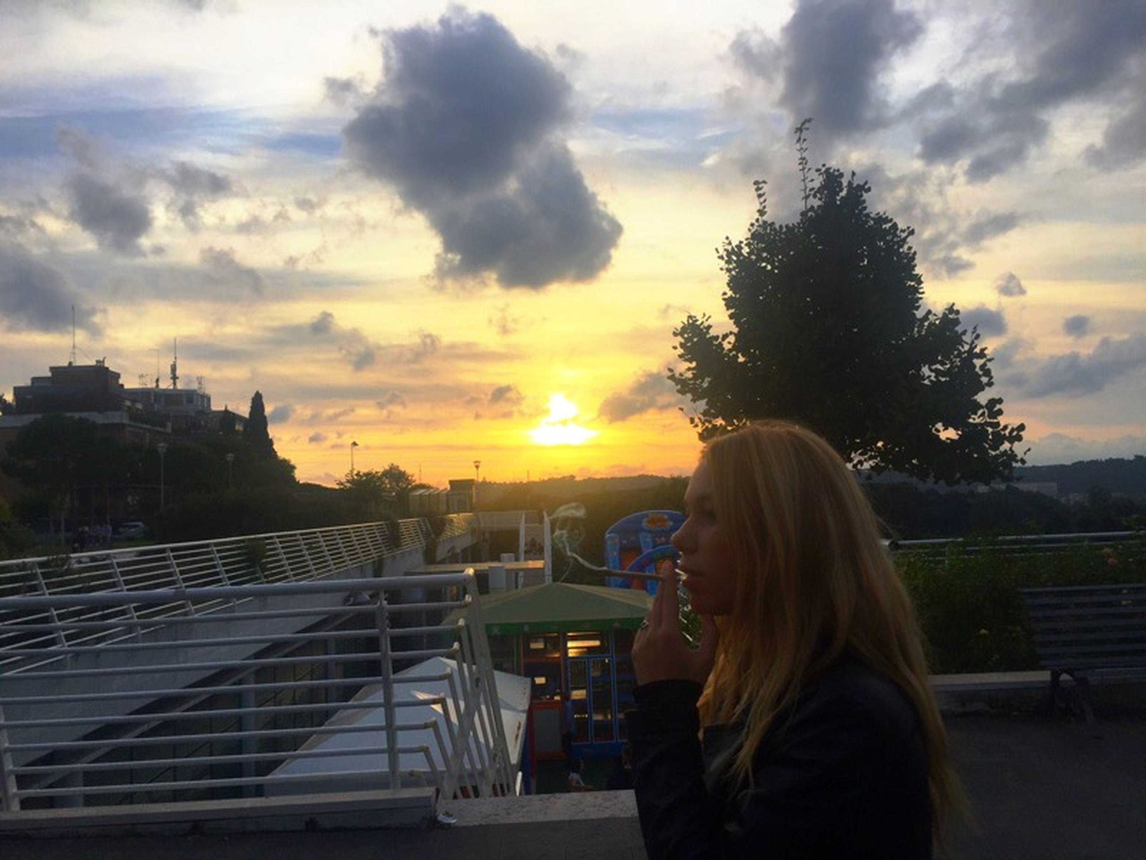 sunset, sky, lifestyles, leisure activity, rear view, cloud - sky, person, waist up, sitting, orange color, building exterior, casual clothing, cloud, sun, transportation, long hair, built structure, standing