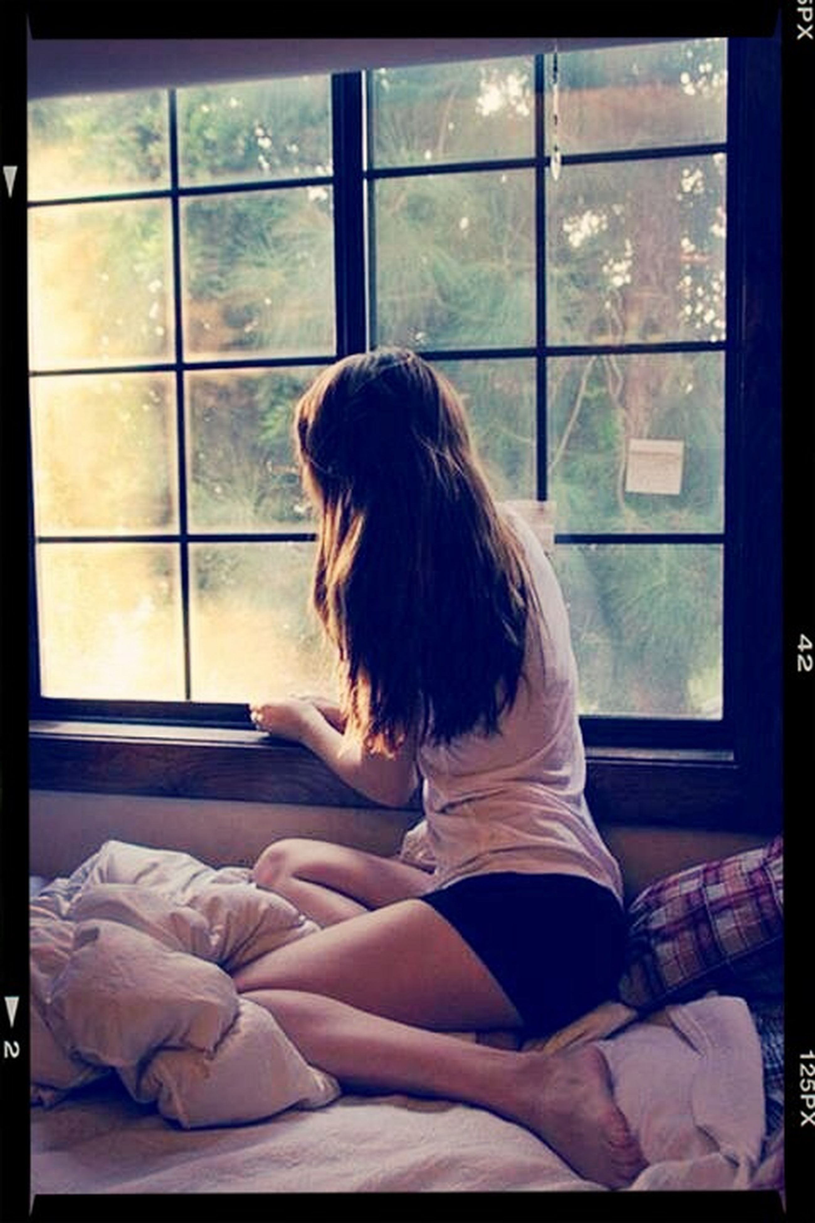 window, indoors, rear view, transfer print, glass - material, transparent, lifestyles, person, looking through window, sitting, auto post production filter, leisure activity, long hair, men, standing, relaxation, waist up, curtain