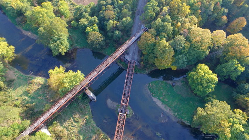Aerial view of intersecting train tracks over a creek Tree Bridge - Man Made Structure No People Outdoors Nature Sky Beauty In Nature Growth Train Tracks Creekside Photography Aerial View Aerial Shot Green Color