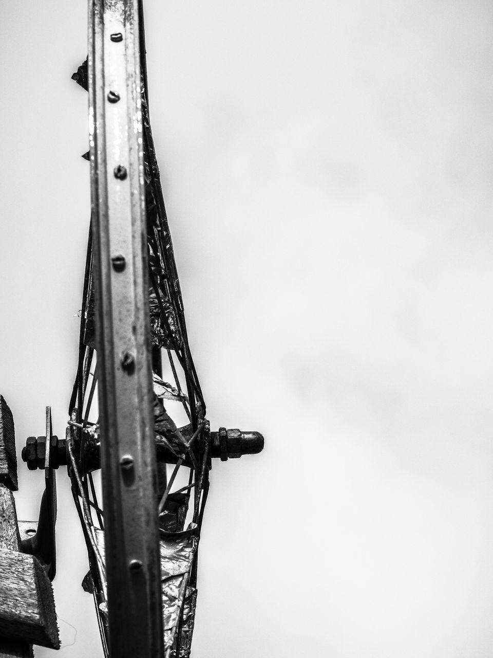 Close-Up Of Metal Wheel Against Sky