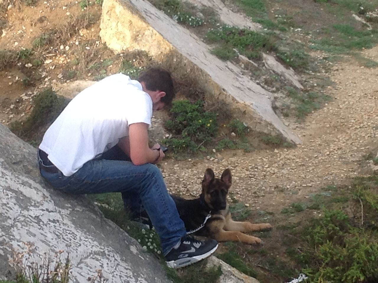 real people, one animal, pets, mammal, domestic animals, outdoors, sitting, day, high angle view, one person, leisure activity, casual clothing, lifestyles, rock - object, nature, full length, men, dog, bonding