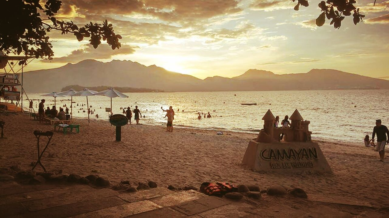 beach, sand, sea, sunset, vacations, water, shore, nature, sky, large group of people, outdoors, leisure activity, enjoyment, cloud - sky, beauty in nature, travel destinations, scenics, horizon over water, summer, mountain, lifestyles, real people, women, day, beach volleyball, people, adult, adults only