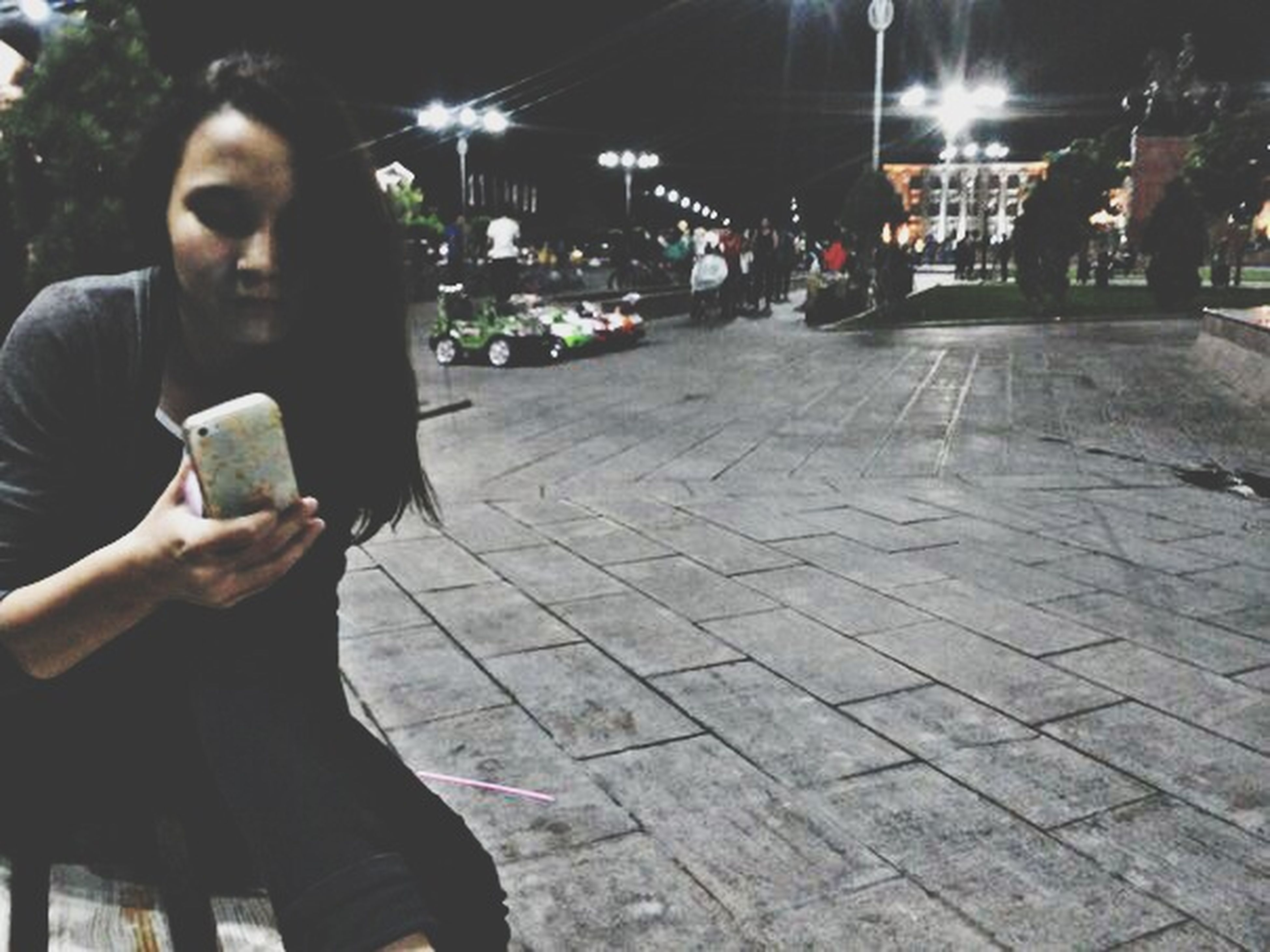 lifestyles, night, leisure activity, casual clothing, illuminated, young adult, standing, full length, person, street, young women, front view, sitting, three quarter length, city life, sidewalk, city