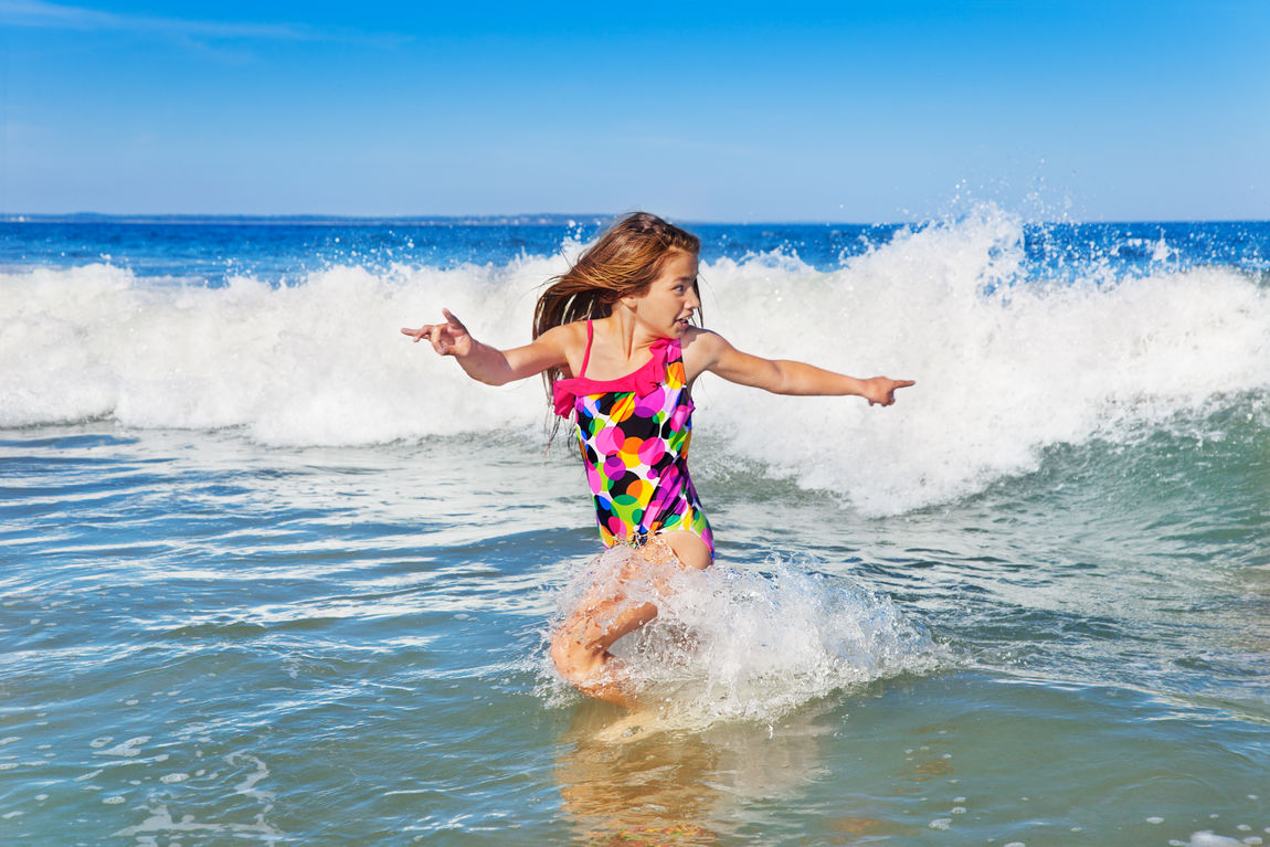 Young girl turning to run from an incoming wave Maine Running Swimming Beach Child Coast Full Length Fun Girls Hurrying Long Hair Motion Ocean One Person Outdoors Playing Real People Sea Shore Splashing Summer Vacations Water Wave Young Girl