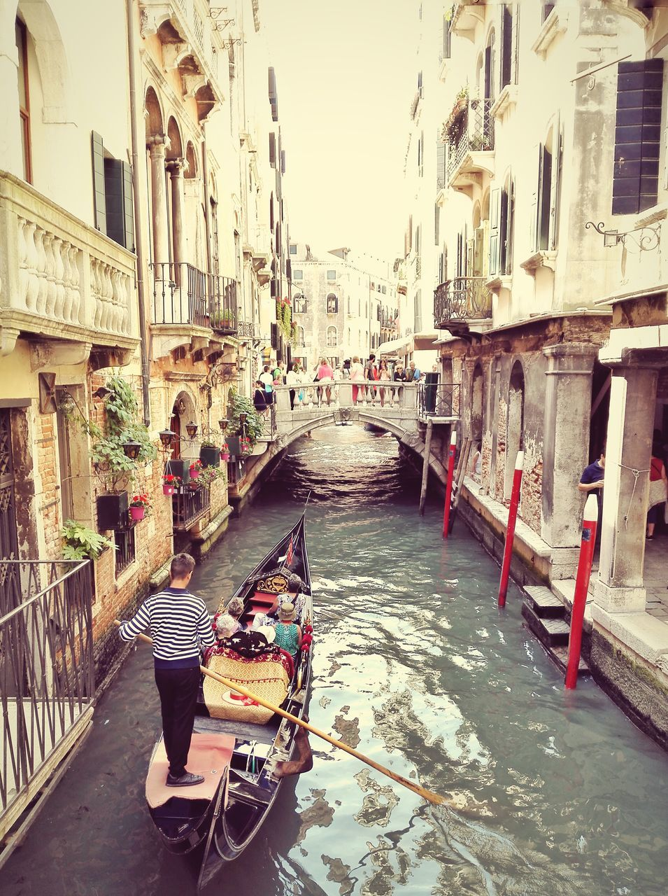 Man with tourist on gondola in canal amidst buildings