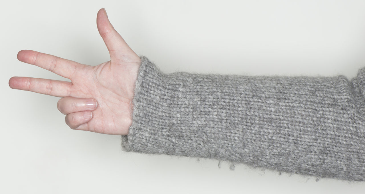 hand shows a gesture as a sign language Arm Body Part Concept Exemptly Finger Fist Flawlessly Forefinger Gesture Gestures Human Body Part Human Hand Sensually Strong Sign Language Snugly Stretching Symbol Thumb Wool