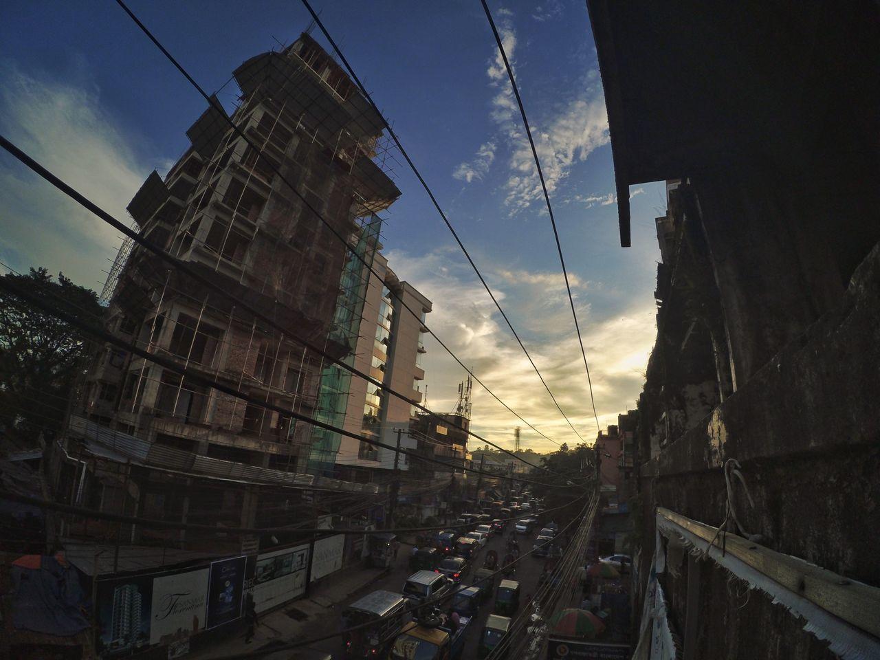 sky, architecture, transportation, building exterior, cable, built structure, cloud - sky, car, road, city, electricity pylon, outdoors, land vehicle, no people, day