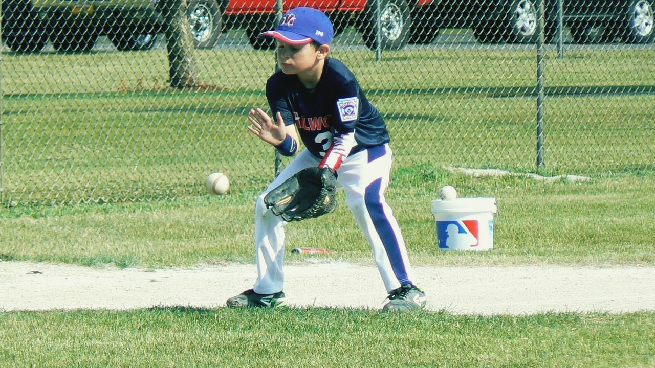 sport, sports uniform, sports helmet, real people, one person, lifestyles, helmet, leisure activity, baseball - sport, front view, headwear, full length, day, baseball uniform, baseball helmet, playing, sports clothing, outdoors, competition, grass, young adult, people, adult, adults only