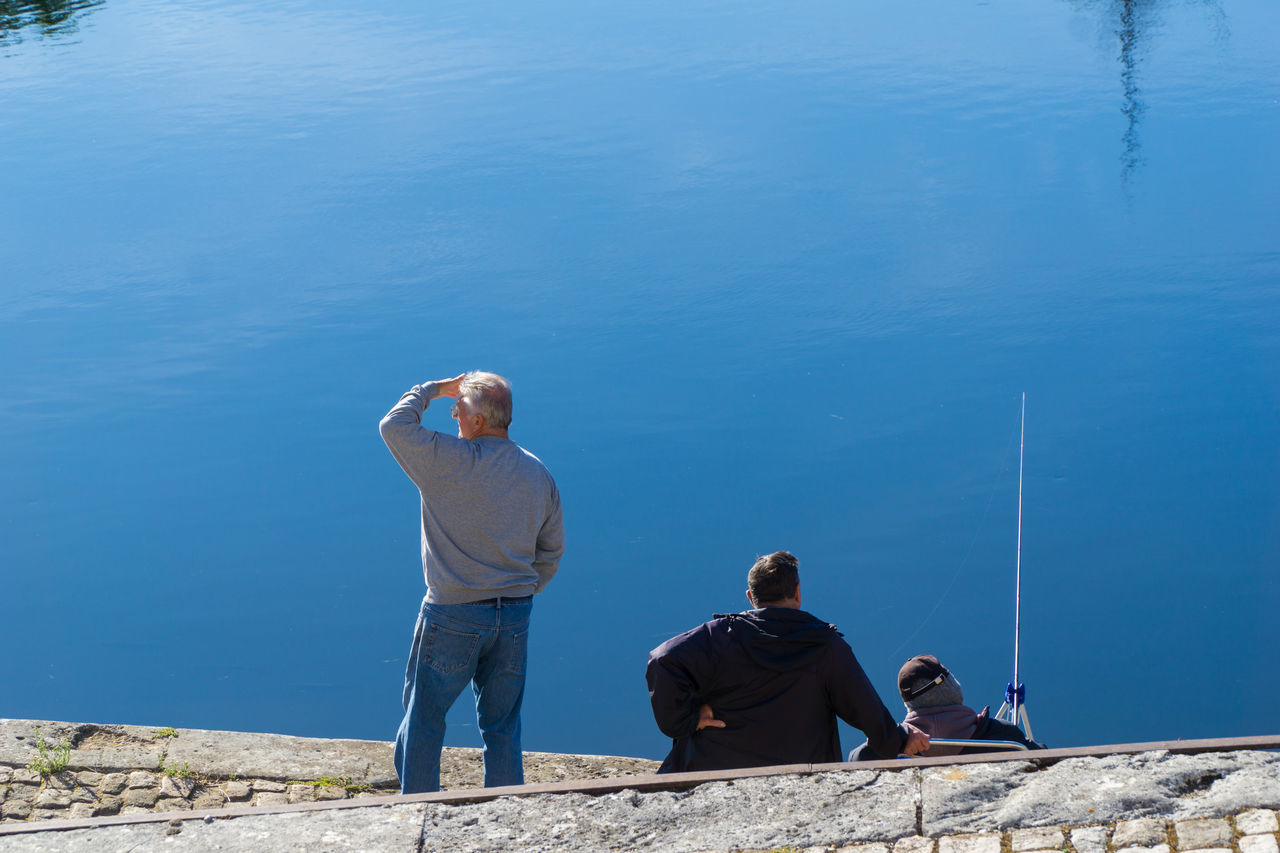 real people, water, senior men, two people, sitting, nature, leisure activity, rear view, day, blue, senior adult, outdoors, standing, full length, togetherness, casual clothing, men, sea, beauty in nature, lifestyles, fishing pole, scenics