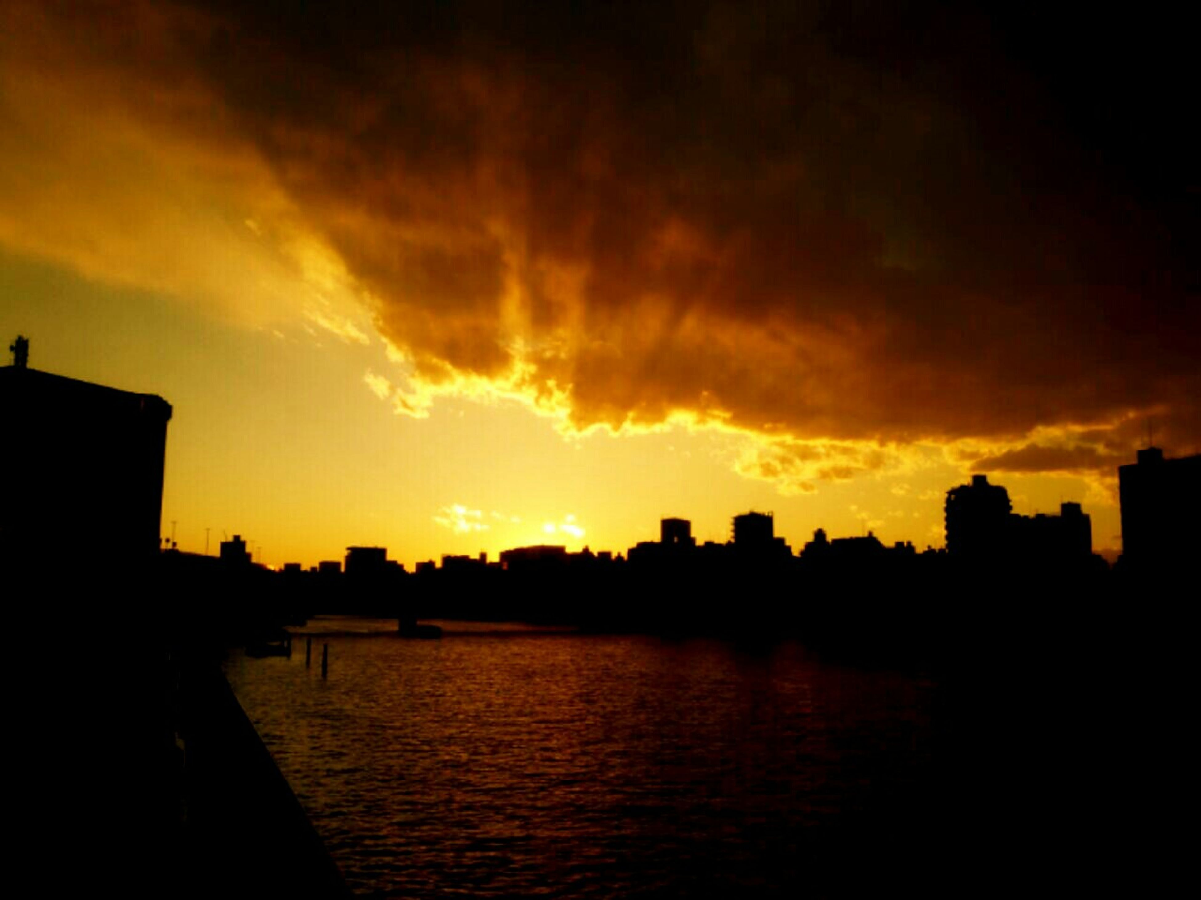 sunset, silhouette, building exterior, architecture, sky, built structure, orange color, water, cloud - sky, scenics, waterfront, city, beauty in nature, cloud, dramatic sky, river, tranquility, moody sky, tranquil scene, nature