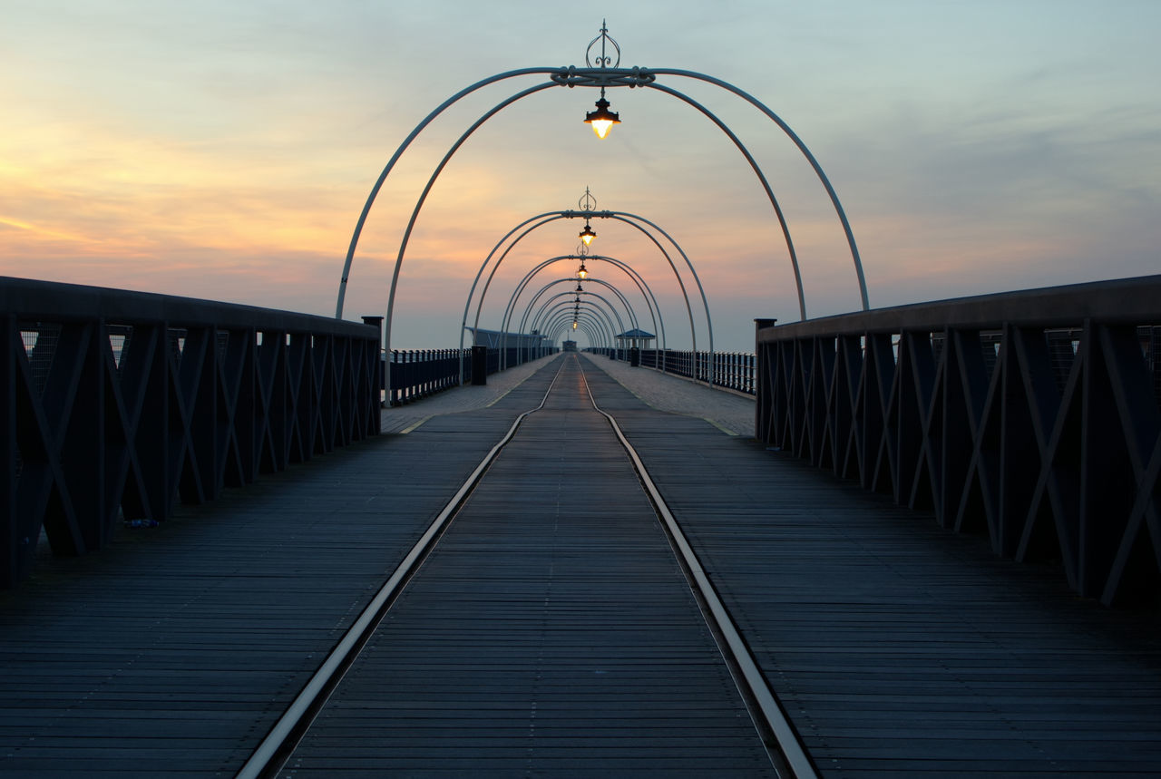 the way forward, diminishing perspective, sunset, railing, bridge - man made structure, built structure, connection, sky, architecture, footbridge, outdoors, no people, water, nature, day