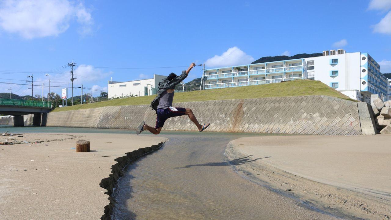 Full Length Of Man Jumping Over Stream Against Sky