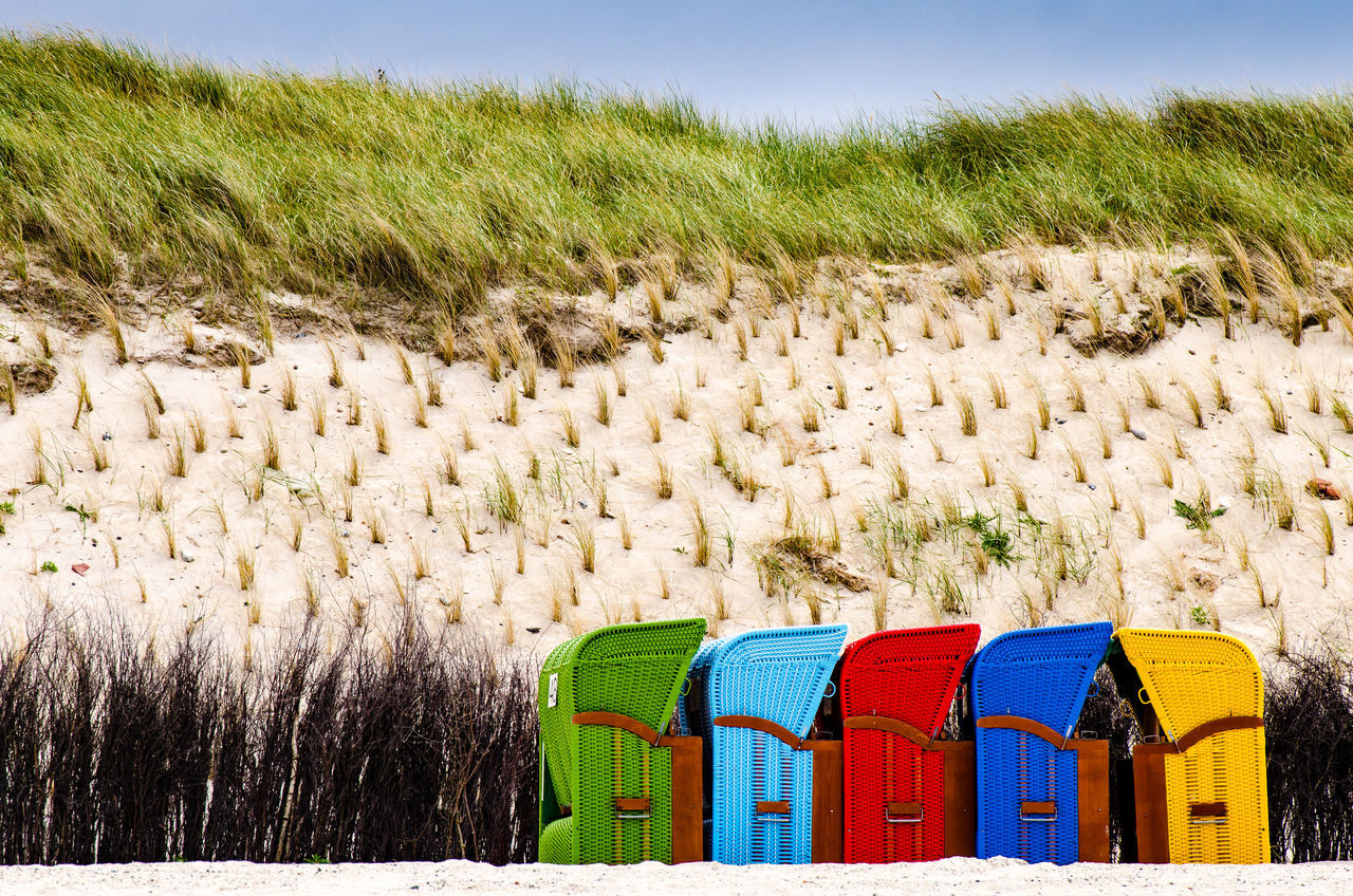 beachchairs, different colors standing together Basket Beach Beachchair Beachchairs Beachday Beachlife Blue Color Color Image Collection Colorful Dry Green Nature No People Red Rural Scene Sand Dune Season  Sky Summer Yellow