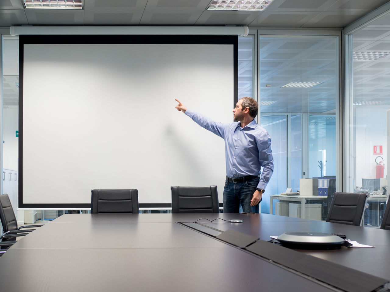 Businessman Pointing Towards Projection Screen While Standing In Board Room At Office