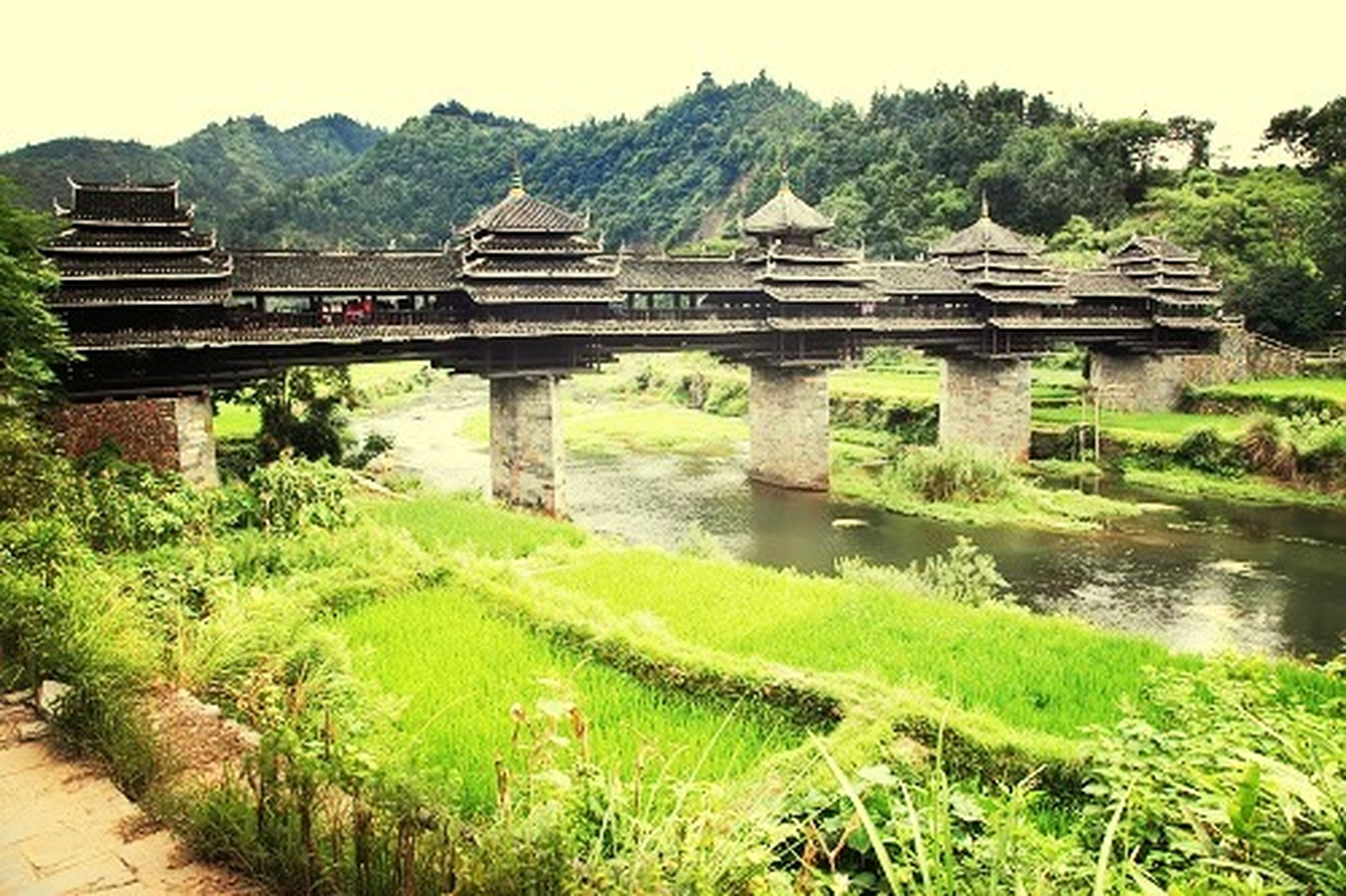 built structure, architecture, water, grass, bridge - man made structure, mountain, river, connection, history, building exterior, tree, old ruin, tranquility, travel destinations, nature, green color, clear sky, scenics, travel, plant