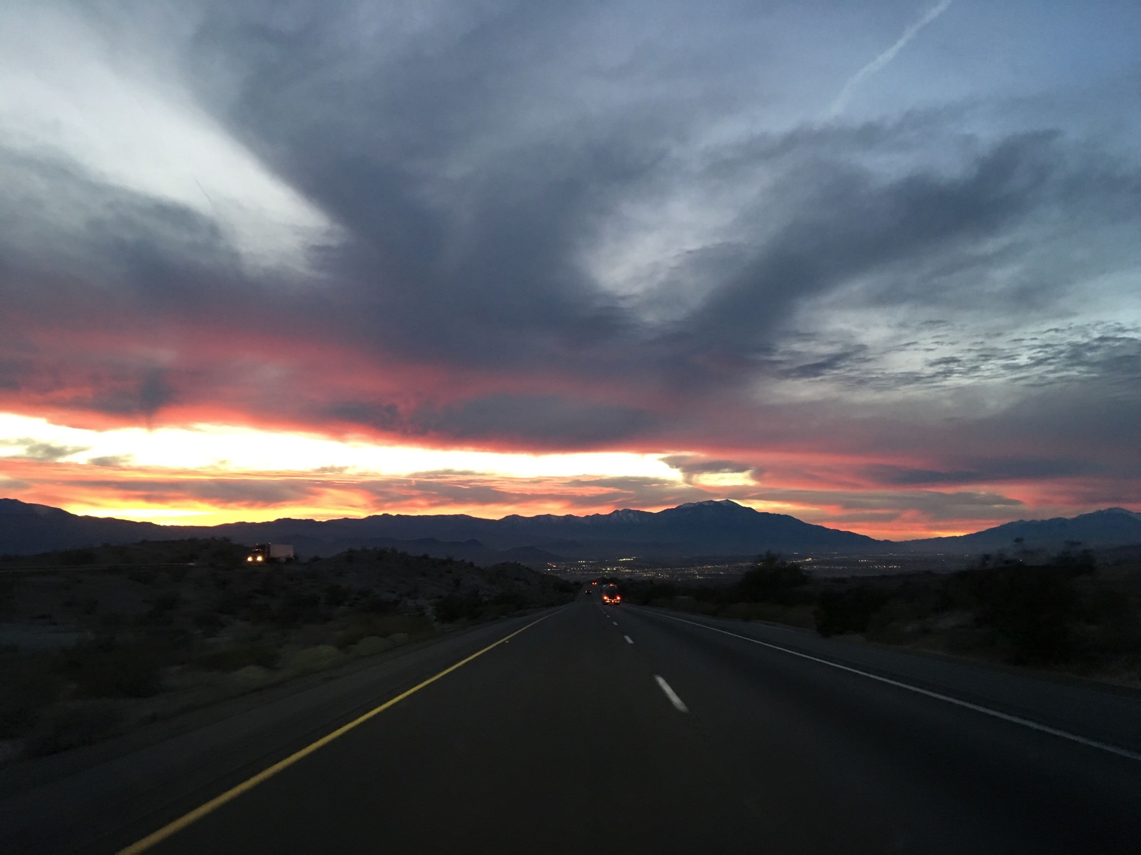 road, transportation, the way forward, sunset, sky, mountain, road marking, cloud - sky, diminishing perspective, country road, scenics, landscape, tranquil scene, beauty in nature, vanishing point, tranquility, nature, mountain range, orange color, cloud