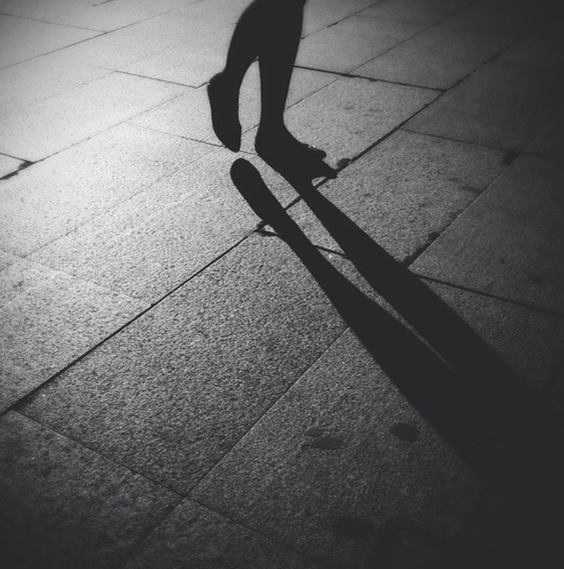 shadow, high angle view, walking, men, low section, street, lifestyles, sunlight, tiled floor, person, unrecognizable person, silhouette, sidewalk, pavement, outdoors, full length, paving stone, day