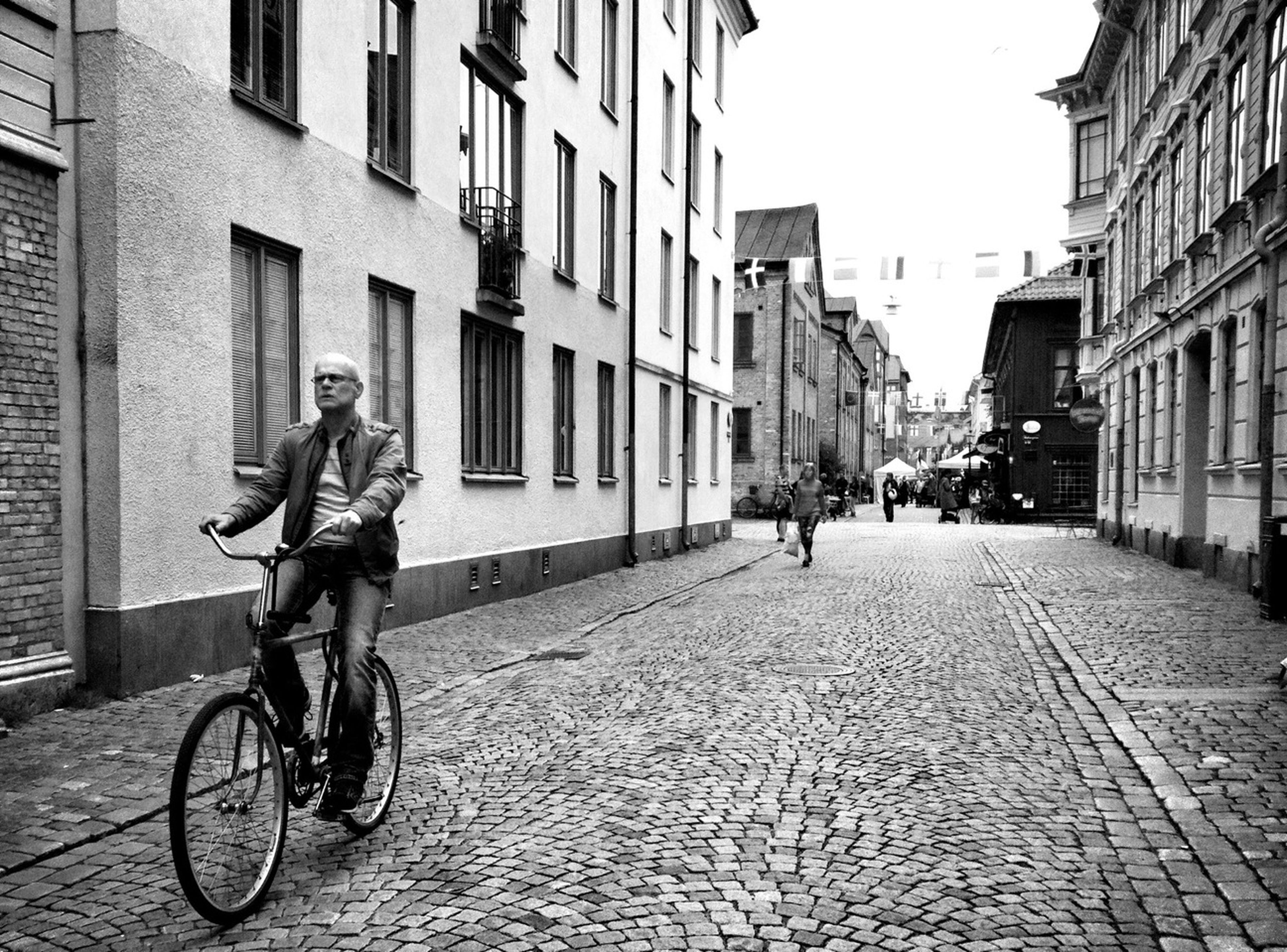 bicycle, building exterior, architecture, built structure, full length, transportation, lifestyles, mode of transport, street, riding, city, men, land vehicle, leisure activity, walking, cobblestone, casual clothing, city life