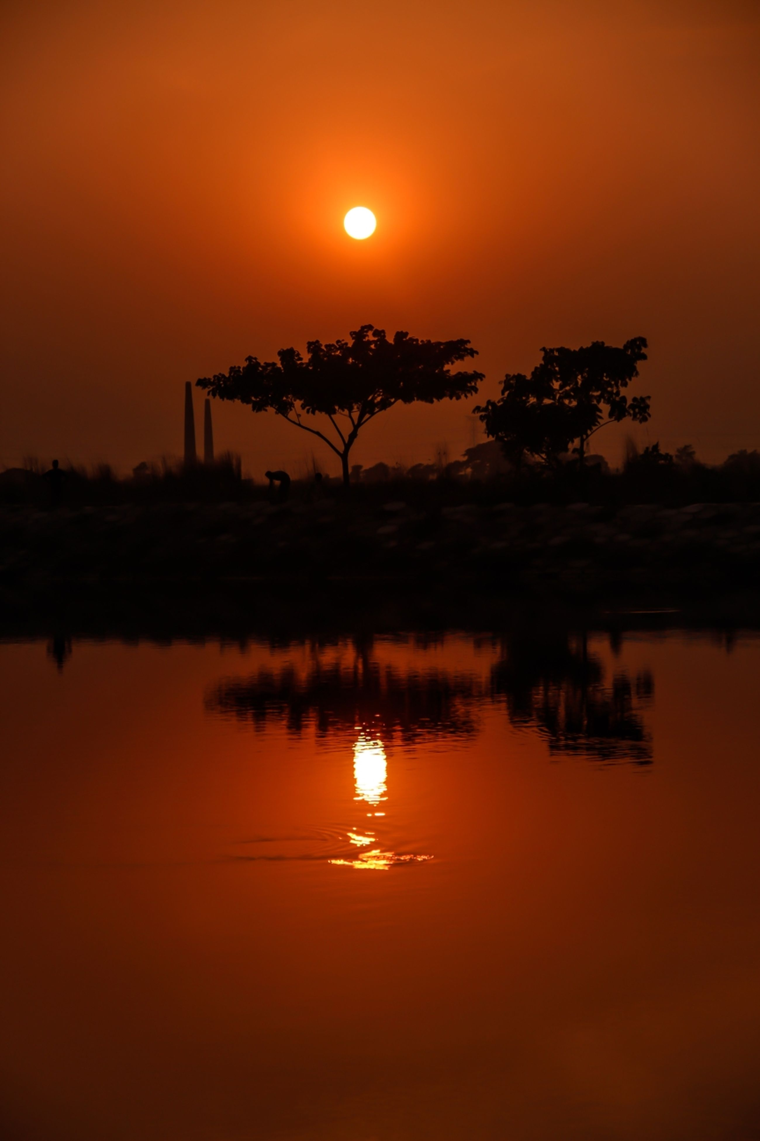 sunset, reflection, sun, water, orange color, scenics, tranquil scene, silhouette, tranquility, beauty in nature, lake, waterfront, idyllic, sky, nature, standing water, tree, built structure, glowing, river