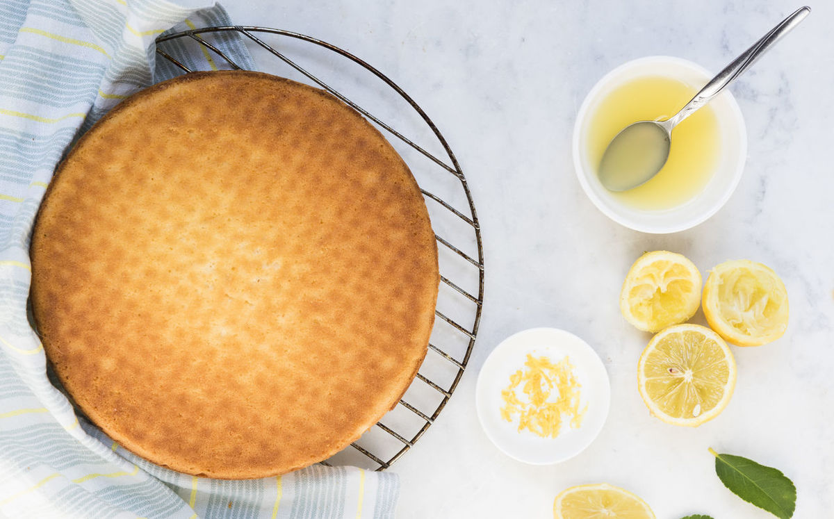 Freshly baked lemon cake with striped blue napkin on a wire cooling rack. Cakes Dessert Horizontal Juice Spoon Bowl Cake Cooling Rack Directly Above Food Fresh Indoors  Lemon Cake Lemon Juice Lemon Juice And Zest Lemon Zest Lemons Ready-to-eat Round Striped Napkin Wire Rack