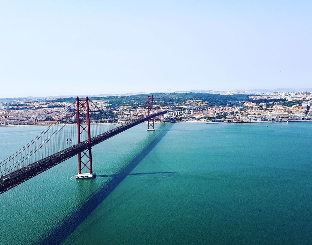 EyeEmNewHere Water Sky Outdoors Day City Cityscape Built Structure Urban Skyline Bridge - Man Made Structure Portugal_lovers Colorful Travel Destinations Travel Blue Igers 25aprilbridge Lisbon Red Metal Infrastructure Architecture Prespective High River The Architect - 2017 EyeEm Awards The Great Outdoors - 2017 EyeEm Awards