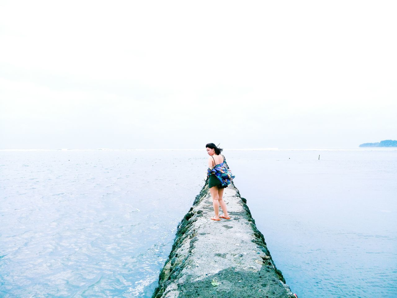 sea, real people, water, nature, one person, horizon over water, beauty in nature, full length, leisure activity, scenics, standing, outdoors, lifestyles, sky, day, rear view, ankle deep in water, clear sky, young adult, people
