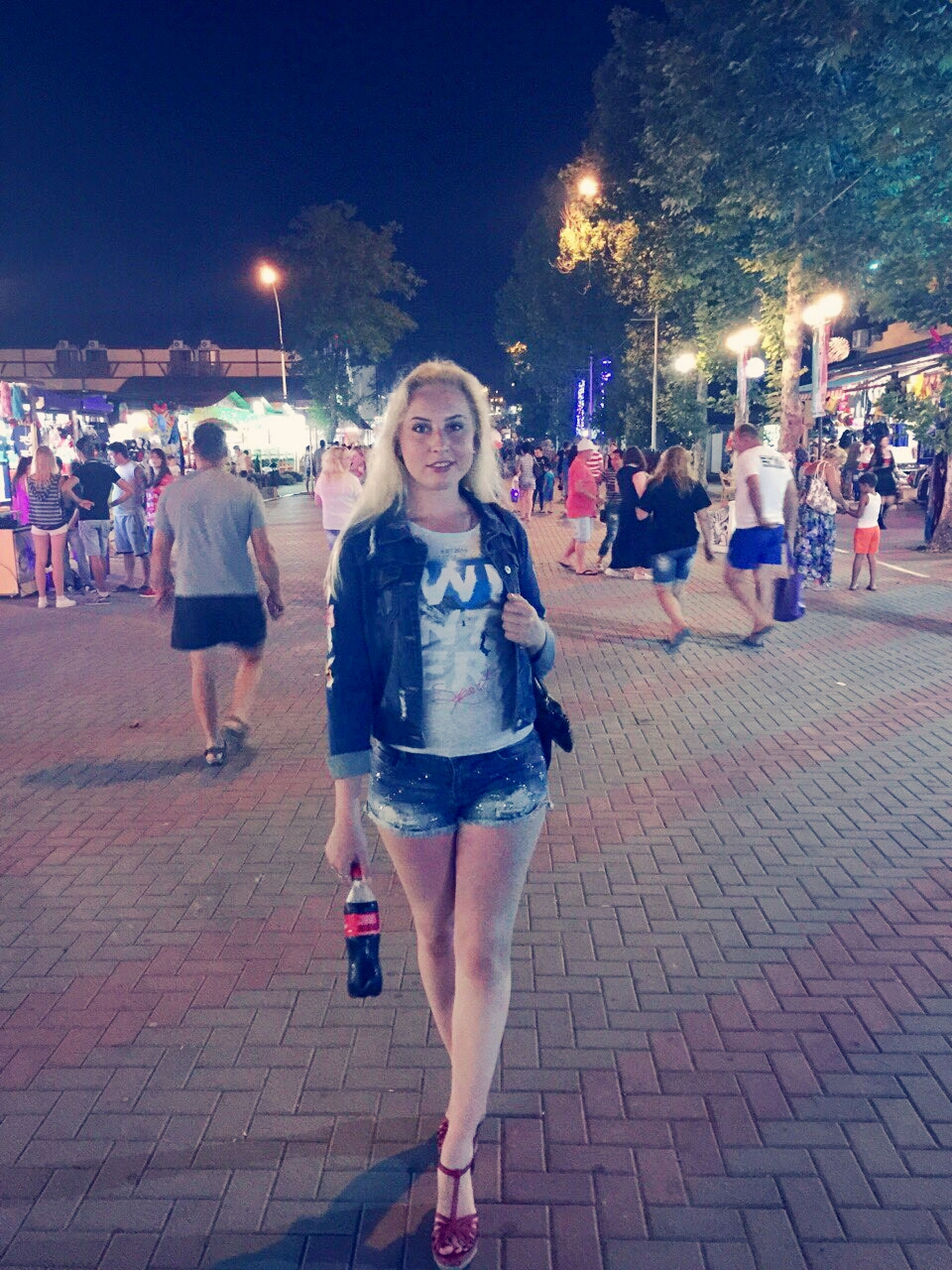 lifestyles, leisure activity, illuminated, casual clothing, standing, night, young women, front view, looking at camera, young adult, street, enjoyment, portrait, person, happiness, building exterior, incidental people