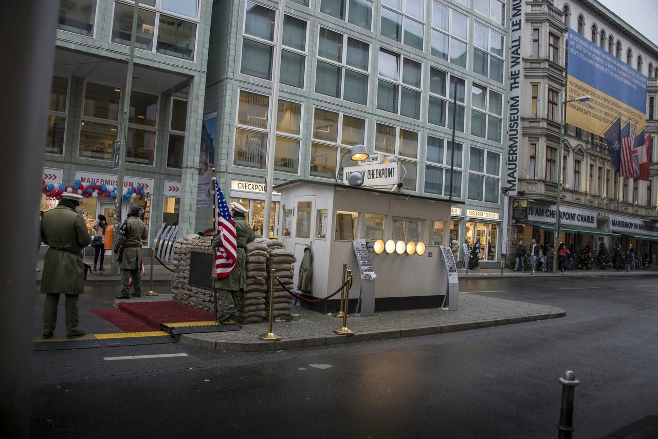 "Checkpoint Charlie (or ""Checkpoint C"") was the name given by the Western Allies to the best-known Berlin Wall crossing point between East Berlin and West Berlin during the Cold War (1947-1991). GDR leader Walter Ulbricht agitated and maneuvered to get the Soviet Union's permission to construct the Berlin Wall in 1961 to stop Eastern Bloc emigration westward through the Soviet border system, preventing escape across the city sector border from communist East Berlin into free West Berlin. Checkpoint Charlie became a symbol of the Cold War, representing the separation of East and West. (🕵spying on checkpoint charlie🕵) Checkpointcharlie Checkpoint Charlie  Berlin Germany Army US Flag USA FLAG Flag Military Cold War Police Police Officers Policeman Policemen Adult People Streetphotography Street Photography Exceptional Photographs Building Exterior Adults Only Military Uniform Military Police Holiday Vacations Finding New Frontiers Traveling Home For The Holidays"