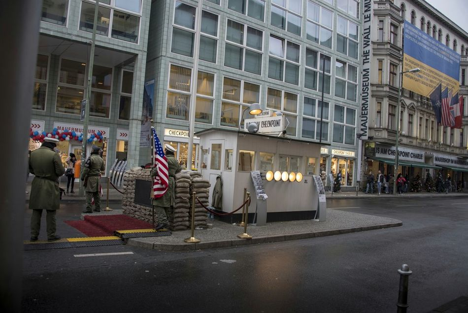 """Checkpoint Charlie (or """"Checkpoint C"""") was the name given by the Western Allies to the best-known Berlin Wall crossing point between East Berlin and West Berlin during the Cold War (1947-1991). GDR leader Walter Ulbricht agitated and maneuvered to get the Soviet Union's permission to construct the Berlin Wall in 1961 to stop Eastern Bloc emigration westward through the Soviet border system, preventing escape across the city sector border from communist East Berlin into free West Berlin. Checkpoint Charlie became a symbol of the Cold War, representing the separation of East and West. (🕵spying on checkpoint charlie🕵) Checkpointcharlie Checkpoint Charlie  Berlin Germany Army US Flag USA FLAG Flag Military Cold War Police Police Officers Policeman Policemen Adult People Streetphotography Street Photography Exceptional Photographs Building Exterior Adults Only Military Uniform Military Police Holiday Vacations Finding New Frontiers Traveling Home For The Holidays"""