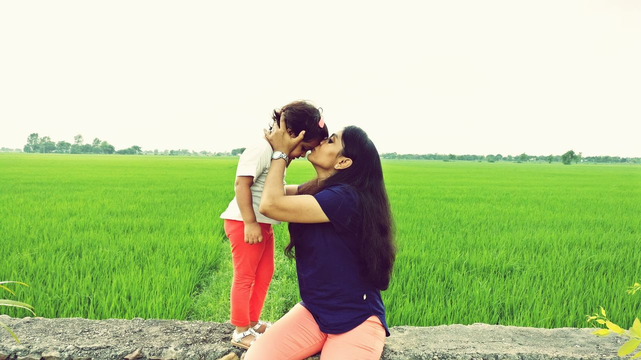 two people, field, young women, real people, young adult, togetherness, love, casual clothing, young men, day, clear sky, young couple, lifestyles, leisure activity, couple - relationship, happiness, outdoors, grass, bonding, landscape, standing, sky, nature, beauty in nature, people