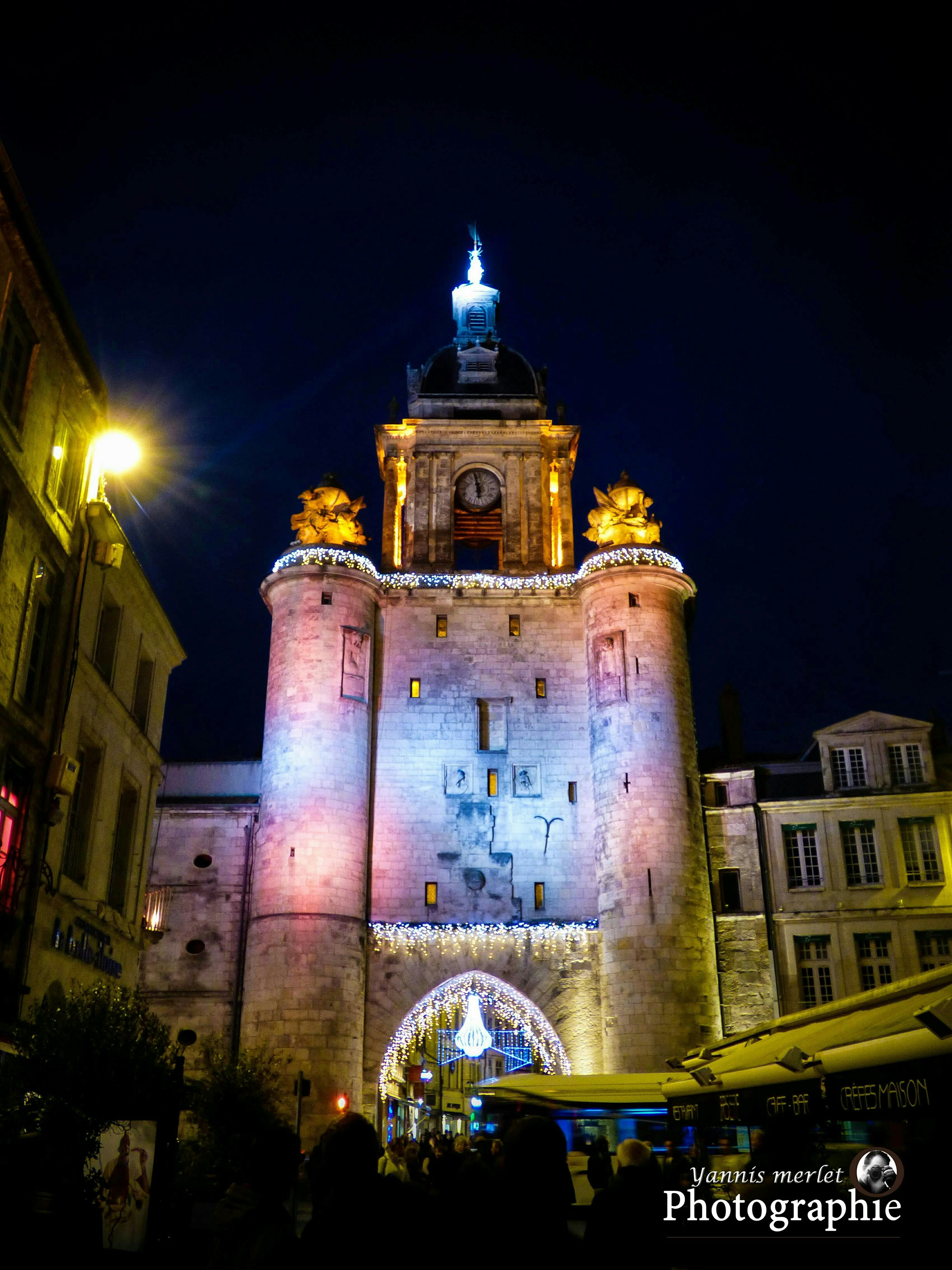 architecture, building exterior, built structure, night, illuminated, low angle view, city, tower, clock tower, arch, sky, clear sky, travel destinations, history, building, travel, famous place, transportation, facade, outdoors