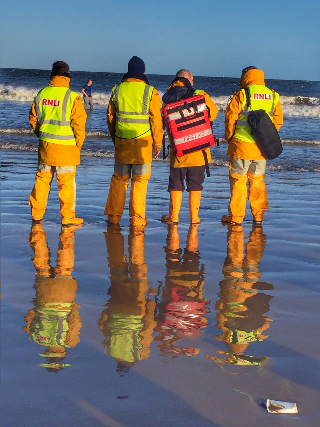 Lifeguards and first aiders on a beach Rear View Reflections Water Real People Sky Sea Outdoors Yellow Horizon Over Water Togetherness Day Beach Men Nature Low Section Winter Beach Teeside Redcar England First Aiders First Aid Sea Lifeguards RNLI
