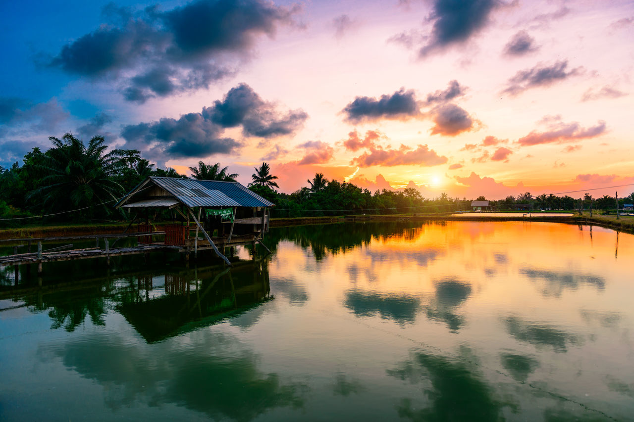 sunset, reflection, water, sky, built structure, scenics, tranquil scene, cloud - sky, tranquility, beauty in nature, nature, outdoors, no people, waterfront, architecture, lake, building exterior, tree, day