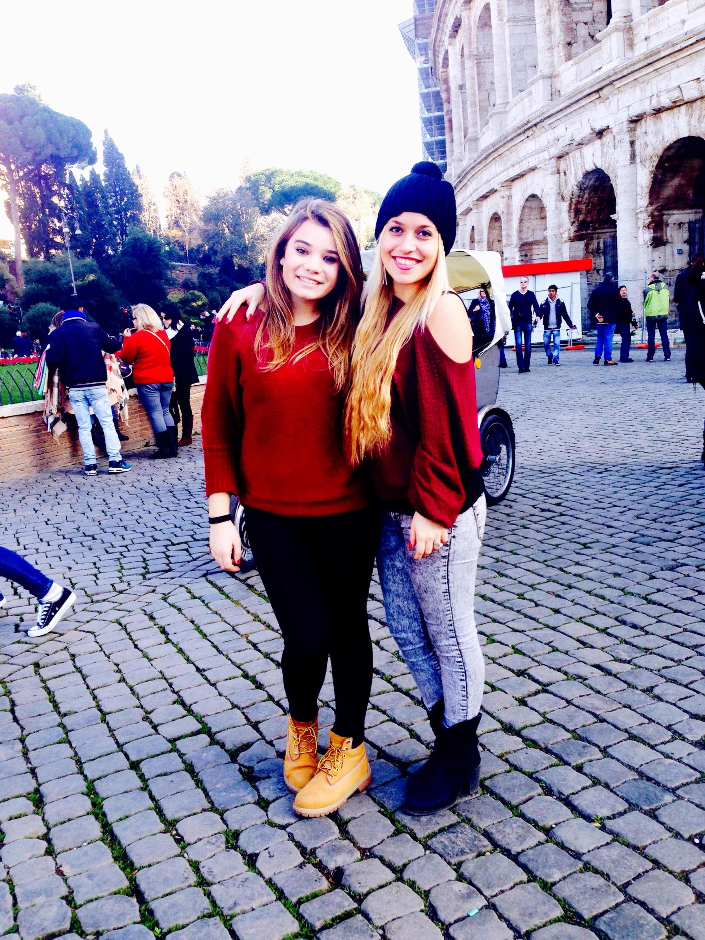 lifestyles, casual clothing, leisure activity, person, looking at camera, portrait, full length, togetherness, front view, smiling, young adult, bonding, happiness, standing, building exterior, young women, cobblestone, built structure