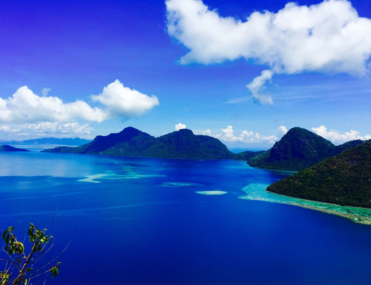Scenic View Of Blue Sea And Mountains Against Cloudy Sky
