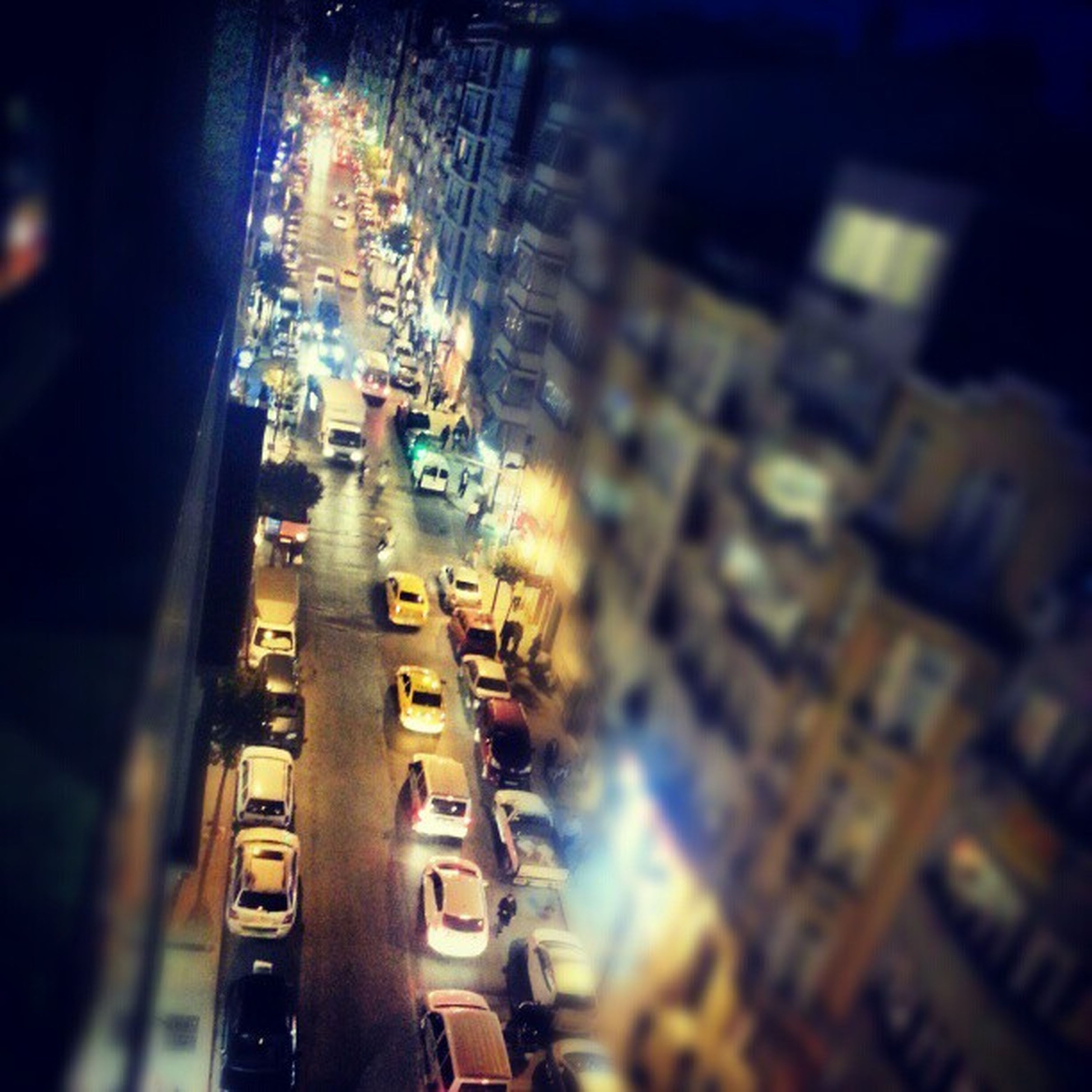 illuminated, night, city, building exterior, architecture, transportation, built structure, mode of transport, city life, high angle view, cityscape, street, city street, land vehicle, car, traffic, travel, road, lighting equipment, light - natural phenomenon