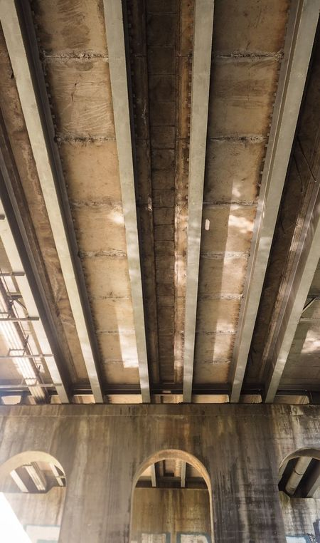 Under the bridge Rust Pipes Graffiti Daylight Concrete Steel Beams Underground Engineering What Lies Beneath Hidden Architecture Arches Grimey Industrial Road Warterway