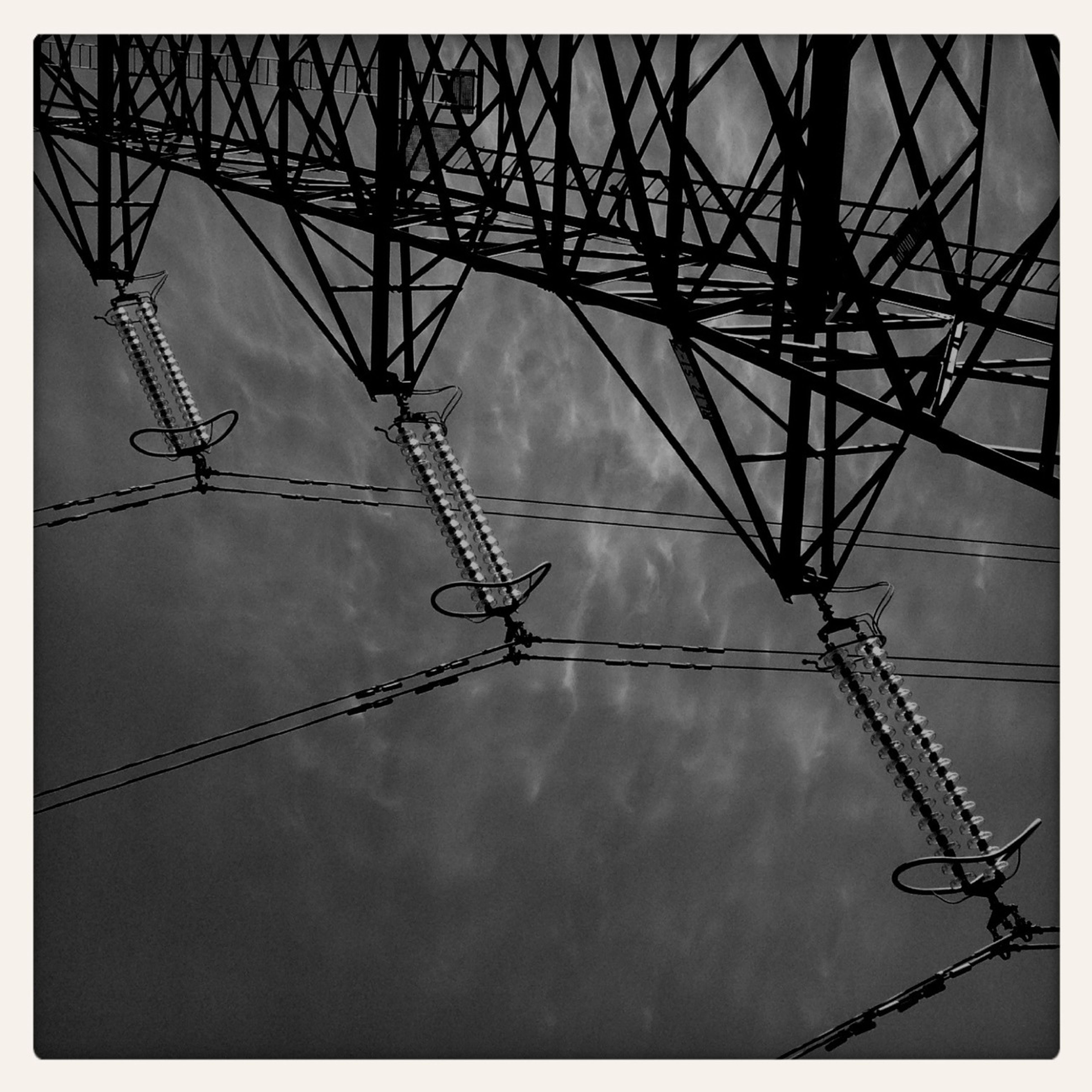 low angle view, electricity pylon, electricity, power line, power supply, fuel and power generation, connection, technology, sky, transfer print, auto post production filter, silhouette, cable, cloud - sky, complexity, built structure, crane - construction machinery, development, construction site, dusk
